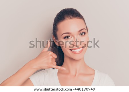 Cheerful playful woman gesturing and assking to call her - stock photo