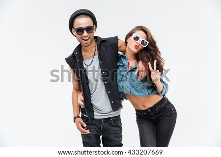 Cheerful playful young couple hugging and showing peace sign over white background - stock photo