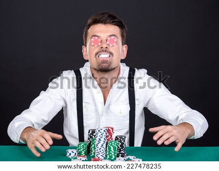 Cheerful poker player with chips on the black background.