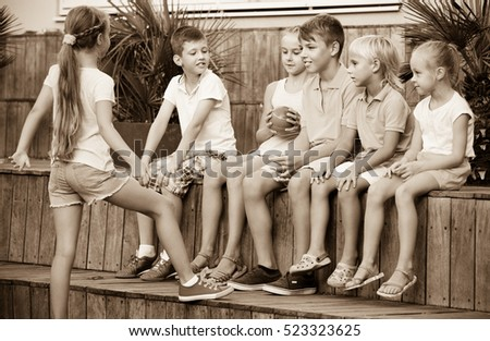 Cheerful positive boys and girls in school age sitting and playing with ball outdoors