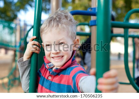 cheerful positive kid spending fun time at the playground - stock photo