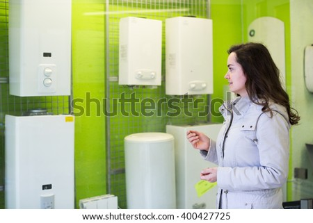 Cheerful positive woman buying new heating water boiler in supermarket - stock photo