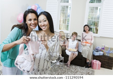 Cheerful pregnant woman and friend holding baby clothes at a baby shower