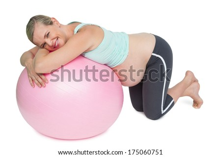 Cheerful pregnant woman kneeling against pink exercise ball on white background