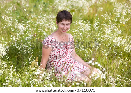 Cheerful pregnant woman sitting in chamomile background - stock photo