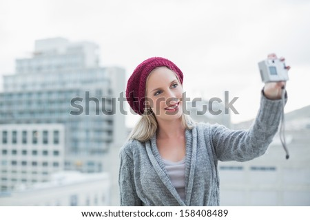 Cheerful pretty blonde taking a self picture outdoors on urban background - stock photo