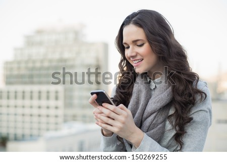 Cheerful pretty brunette in winter clothes sending a text on her smartphone outside on a cloudy day - stock photo