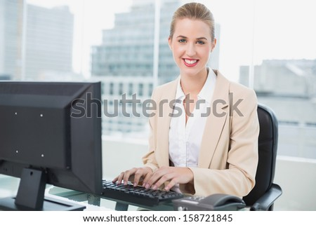 Cheerful pretty businesswoman working on computer in bright office - stock photo