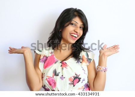 Cheerful pretty girl with perfect smile and white teeth holding copyspace on the palm over white background  - stock photo