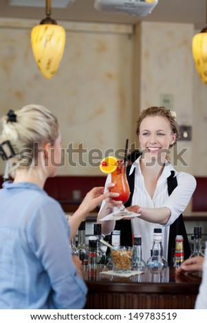 Cheerful pretty waitress giving a fresh tasty cocktail to a blond woman at a bar - stock photo