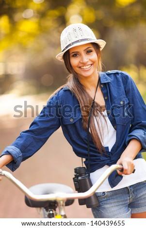 cheerful pretty woman pushing bike and carrying binoculars at park - stock photo