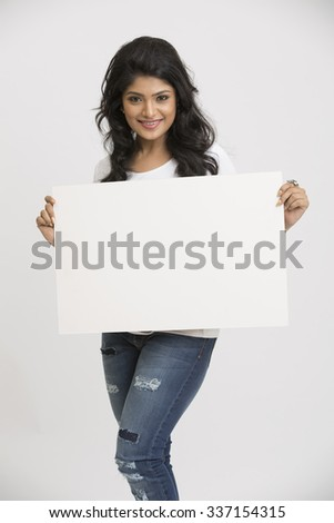 Cheerful pretty young Indian woman holding a blank billboard white background - stock photo
