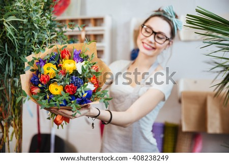 Cheerful pretty young woman florist in glasses showing bouquet of colorful flowers  - stock photo