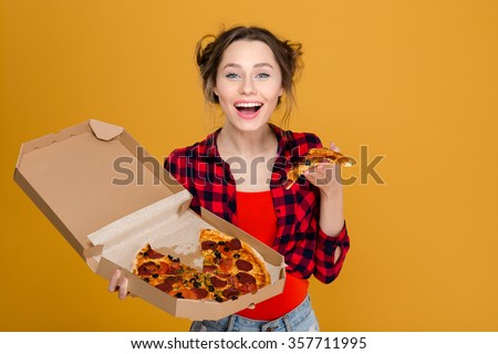Cheerful pretty young woman in plaid shirt enjoying pizza over yellow background - stock photo