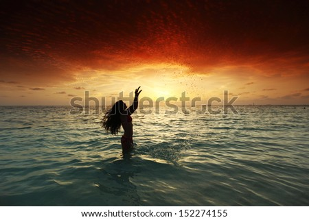 Cheerful pretty young woman splashin in sea on sunset - stock photo