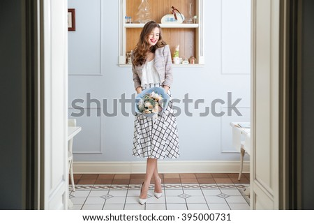 Cheerful pretty young woman with long curly hair standing in cafe and holding bouquet of flowers - stock photo
