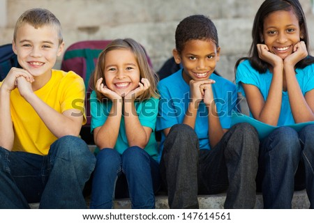 cheerful primary school children sitting outdoors - stock photo