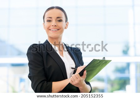 Cheerful recruit. Beautiful young woman in formalwear writing something in clipboard and smiling while standing outdoors - stock photo