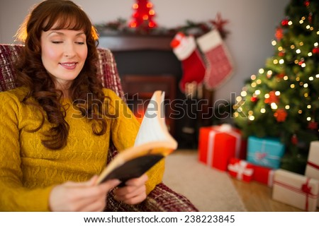 Cheerful red hair reading a book at christmas at home in the living room - stock photo