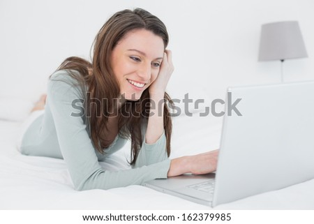Cheerful relaxed casual young woman with laptop in bed at home - stock photo