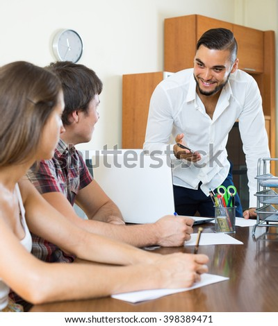 Cheerful salesman telling to colleagues about the project in the office