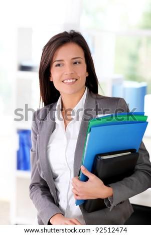 Cheerful saleswoman holding files - stock photo