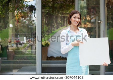Cheerful saleswoman is standing near her flower shop. She is holding an empty white billboard and pointing her finger at it. The woman is looking forward and smiling. Copy space in left side - stock photo