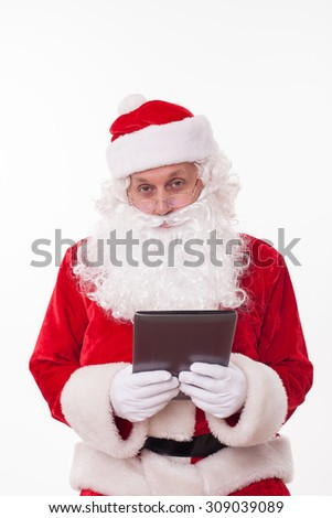 Cheerful Santa Claus is holding a tablet in his hands. He is looking forward sadly. The human wishes have changed. Isolated on background - stock photo