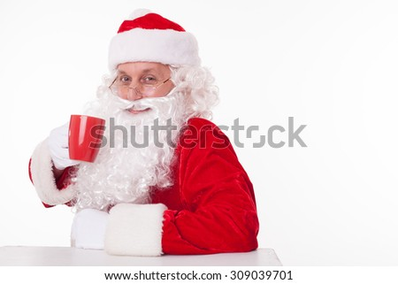 Cheerful Santa Claus is sitting at the table and relaxing. He is holding a cup and drinking tea with pleasure. The man is smiling and looking forward happily. Isolated and copy space in right side - stock photo