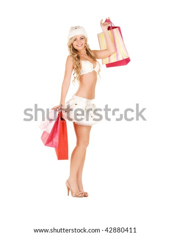 cheerful santa helper with shopping bags over white - stock photo