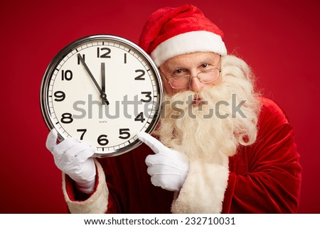 Cheerful Santa pointing at clock in his hand and looking at camera - stock photo