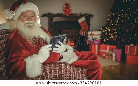 Cheerful santa using tablet on the couch at home in the living room - stock photo