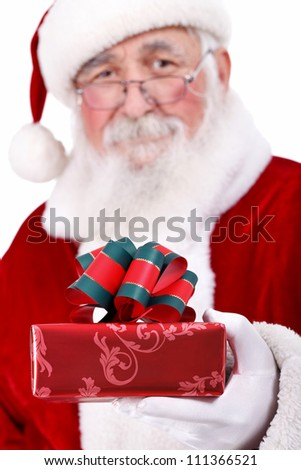 cheerful  Santa with real beard offering gift , gift box in focus, isolated on white background - stock photo