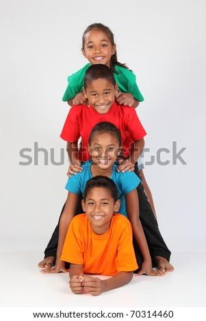 Cheerful school friends form human totem pole - stock photo