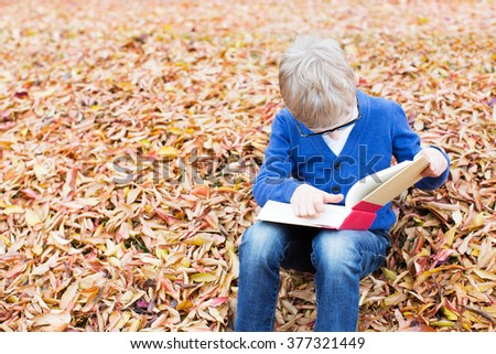 cheerful schoolboy in glasses holding book and ready for school - stock photo