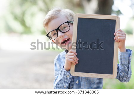 cheerful schoolboy in glasses holding empty blackboard, back to school concept - stock photo