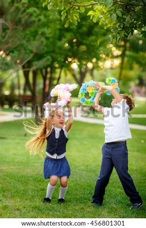 Cheerful schoolchildren playing in the park after school. September 1 - stock photo