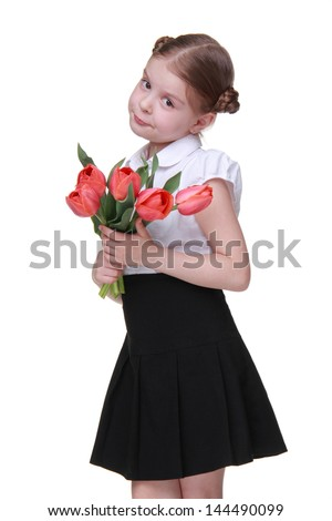 Cheerful schoolgirl wearing white blouse and black skirt and holding bouquet of flowers on Mothers Day
