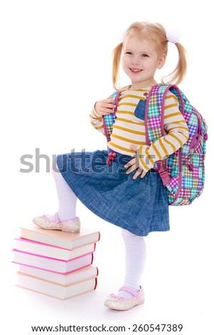 cheerful schoolgirl with satchel behind him holding his leg on a pile of books - isolated on white. - stock photo