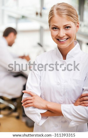 Cheerful scientist. Beautiful young female scientist keeping arms crossed and looking at camera while her male colleague working in the background