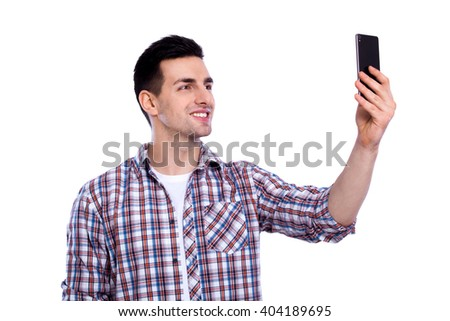 Cheerful selfie. Cheerful young man in shirt holding mobile phone and making photo of himself while standing against white isolated background