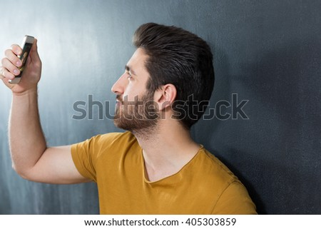 Cheerful selfie. Cheerful young man in shirt holding mobile phone and making photo of himself while standing against grey background
