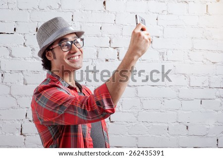 Cheerful selfie. Handsome young Arabic man in shirt holding mobile phone and making photo of himself while standing against brick wall - stock photo