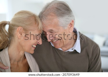 Cheerful senior couple looking at each other's eyes - stock photo