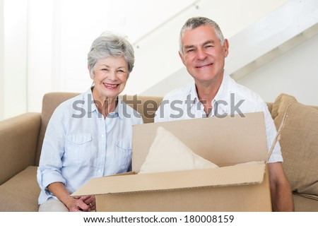 Cheerful senior couple moving into new home smiling at camera - stock photo