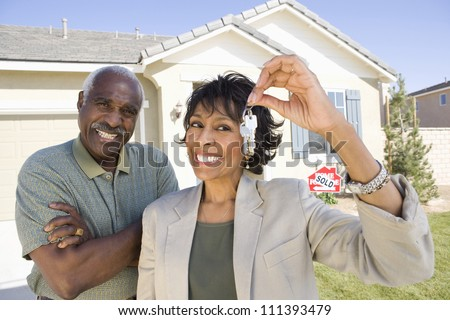 Cheerful senior couple standing in front of house for sale with key - stock photo