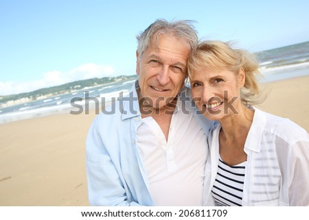 Cheerful senior couple standing on the beach