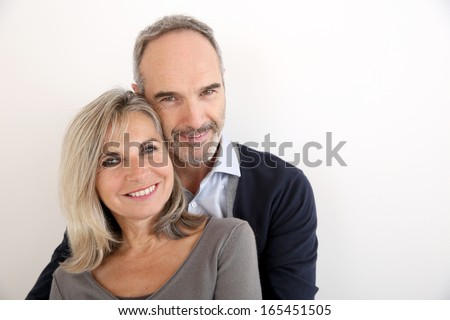 Cheerful senior couple standing on white background - stock photo