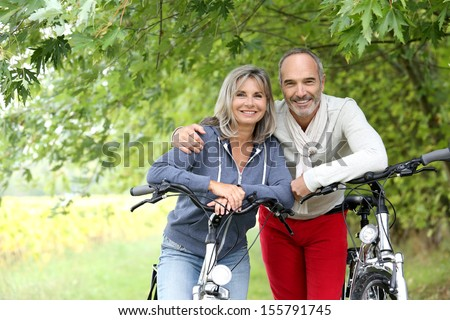 Cheerful senior couple with bicycle in country path - stock photo
