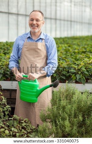 Cheerful senior gardener is pouring water on flowerpots. He is standing and holding container of water. The man is looking at camera and smiling - stock photo